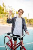 Young man with blond hair in shorts and casual shirt waving and showing hello gesture while standing with bicycle on stock photo