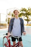 Young man with blond hair standing in shorts and casual shirt with red bicycle on basketball court. Smiling boy holding. Young man with blond hair standing in Royalty Free Stock Image