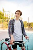 Young man with blond hair standing in shorts and casual shirt with red bicycle on basketball court. Thoughtful boy. Young man with blond hair standing in shorts Royalty Free Stock Photography
