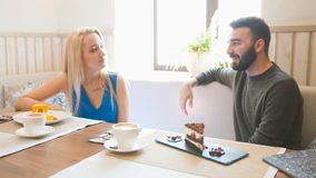Young man and blonde woman takes the cups of coffee at the cafe royalty free stock photos