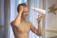 Young man blow drying his hair Royalty Free Stock Images