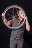 Young man blowing on bike wheel Royalty Free Stock Photos