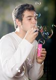 Young man blowing bubbles. Outdoors Royalty Free Stock Photography