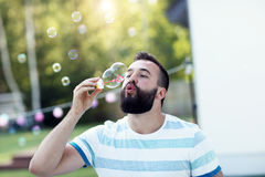 Young man blowing bubbles outdoors Stock Photo
