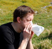 Young man blowing his nose Royalty Free Stock Photo