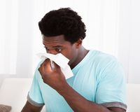 Young man blowing his nose in a tissue Royalty Free Stock Photos