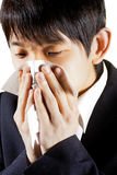 Young Man Blowing Nose into a tissue Royalty Free Stock Images