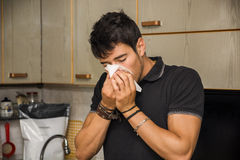 Young Man Blowing Nose into Tissue Royalty Free Stock Photo