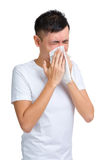 Young man blowing nose using tissue Stock Photos