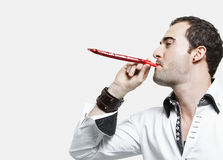 Young man blowing party blower against gray background Royalty Free Stock Photography