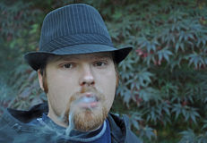 Young Man Blowing Smoke. This young Caucasian man with goatee and wearing a black pin striped hat is blowing smoke Royalty Free Stock Image