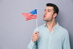 Young man blowing on US flag Royalty Free Stock Image