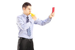 Young man blowing a whistle and showing a red card Stock Images