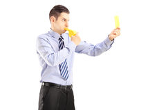 Young man blowing a whistle and showing a yellow card Stock Photo
