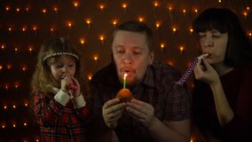 Family together celebrate the holiday. A young man blows a candle on a cupcake, his wife and daughter blowing in colorful party horns. Family together celebrate stock video