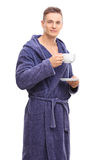 Young man in a blue bathrobe drinking tea Stock Photo