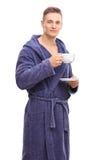 Young man in a blue bathrobe drinking tea Stock Photo