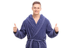 Young man in a blue bathrobe giving thumbs up Stock Images