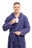 Young man in a blue bathrobe holding a coffee mug Stock Photography