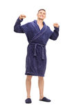 Young man in a blue bathrobe stretching himself Royalty Free Stock Photos