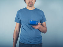 Young man in blue with cappucino Stock Images