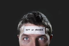 Young man with blue eyes and tape text out of order on forehead in dry empty mind. Young man with blue eyes and tape text out of order on forehead in empty mind Stock Photography
