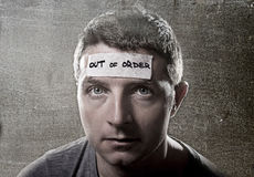 Young man with blue eyes and tape text out of order on forehead in dry empty mind Royalty Free Stock Photo