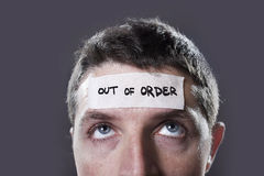 Young man with blue eyes and tape text out of order on forehead in dry empty mind Royalty Free Stock Image