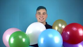A young man with blue hair holds in his hands colorful inflatable balls. Alternative man smiles with balls on a blue