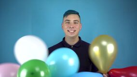 A young man with blue hair holds in his hands colorful inflatable balls. Alternative person having fun with balls on a