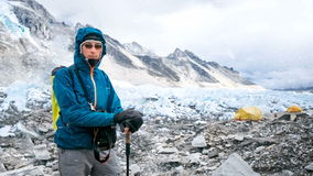 Young man in blue jacket resting after mountain climbing stock video footage