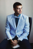 Young man in blue jacket with a white bow tie waits Royalty Free Stock Photography
