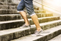 Young man in blue jeans and sneaker shoes walking up stairs outd. Oors background with copy space for text. Concept of person`s lifestyle Royalty Free Stock Images