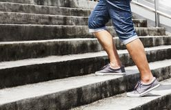 Young man in blue jeans and sneaker shoes walking up stairs outd. Oors background with copy space for text. Concept of person`s lifestyle Royalty Free Stock Photo