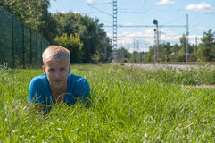 Young man in blue lying on the green grass Royalty Free Stock Photo