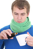Young man in blue with medicine and cup Royalty Free Stock Images