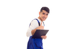 Young man in blue overall holding pen and folder Stock Images