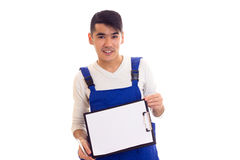 Young man in blue overall holding pen and folder Royalty Free Stock Photography