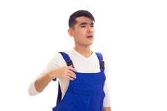 Young man in blue overall looking in a distance. Disturbed young man with dark hair wearing in white shirt and blue overall looking in a distance on white Stock Image