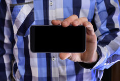 Young man in a blue plaid shirt holding a phone with the black s Stock Photos
