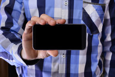 Young man in a blue plaid shirt holding a phone with the black s Royalty Free Stock Photo