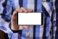 Young man in a blue plaid shirt holding a phone with the white s Royalty Free Stock Photo