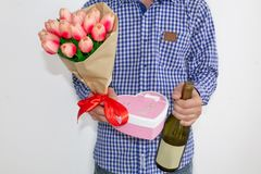 A young man in a blue plaid shirt and jeans, holding a bouquet of tulips, a heart-shaped gift box and a bottle of wine royalty free stock photo