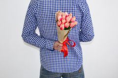 A young man in a blue plaid shirt and jeans, holding a bouquet of tulips, in his hand behind his back, on a white background. royalty free stock photography