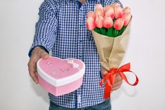 A young man in a blue plaid shirt and jeans, holding out a bouquet of tulips and a heart-shaped gift box, on a white background. stock photos