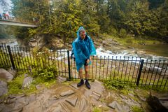 Young man in blue raincoat stands in rain royalty free stock image