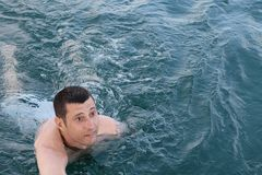 Young man in the blue sea stock photos