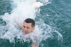 Young man in the blue sea struggling with the waves royalty free stock image