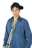 A young man in a blue shirt and a black cap. Half-length portrait of young dark-haired man in a blue plaid shirt and tie stock photography