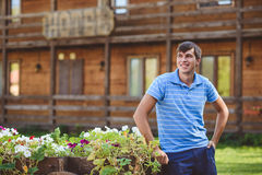 A young man in a blue shirt and blue shorts near decorative wooden carts with flowers, on a background of rustic style. Smiling, looking to the side Stock Photography